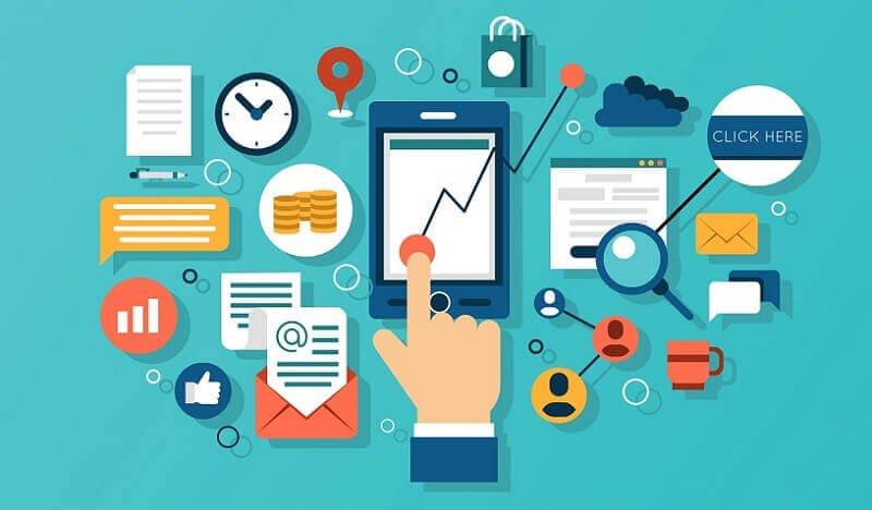 Mão clicando em gráficos em um celular, relógio, carta, lupa, nuvem, símbolo de curtida e xícara de café sugerindo análise de modelos de marketing digital para empresas.